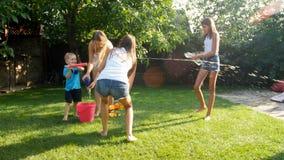 4k materiał filmowy szczęśliwi rozochoceni nastolatkowie bawić się w ogródzie z wodnymi pistoletami i bryzga wodę nad each inny zbiory wideo