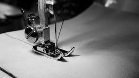 4k materiał filmowy zamyka up szwalnej maszyny igła na białej tkaninie z zwolnionym tempem, czarny i biały kolor zbiory