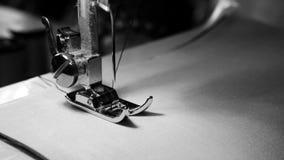 4k materiał filmowy zamyka up szwalnej maszyny igła na białej tkaninie z zwolnionym tempem, czarny i biały kolor zbiory wideo