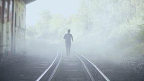 4K mens die snel op mistige treinsporen weglopen Achter mening Abstract schot als achtergrond Het creatieve schot van de levensst stock footage