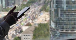 4k, menschlich unter Verwendung eines Smartphone mit Geschäftsgebäude u. Stadtverkehrhintergrund stock video