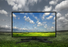 4k Modern television on a green meadow, showing the colors more. Modern television on a green meadow, showing the colors more beautiful than reality Royalty Free Stock Photos