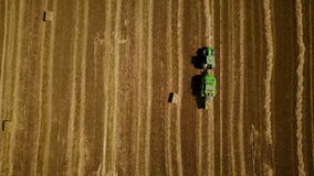 4K. Modern tractor makes haystacks on the field after harvesting. Aerial top view stock video footage