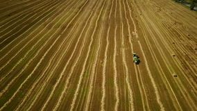 4K. Modern tractor makes haystacks on the field after harvesting. Aerial view stock video footage