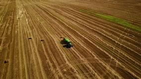 4K. Modern tractor makes haystacks on the field after harvesting. Aerial view stock video