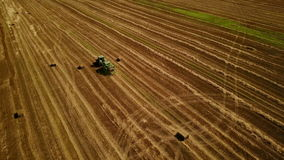 4K. Modern tractor makes haystacks on the field after harvesting. Aerial view stock footage