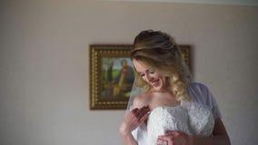 4K mooie bruid die op haar kleding in huwelijkswinkel proberen Langzame Motie stock videobeelden