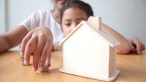 4K Mother and Asian little girl putting money coin to house piggy bank select focus on house.  stock video