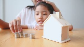 4K Mother and Asian little girl putting money coin to house piggy bank select focus on house.  stock video footage