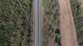 4k motiom powietrzny widok droga wśrodku lasowego paska zbiory