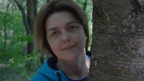 4k movimento lento - suportes da mulher da Idade Média perto da árvore e do sorriso video estoque