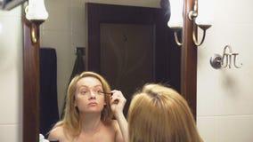 4K Movimento lento Una donna dipinge i suoi cigli davanti ad uno specchio nel bagno archivi video