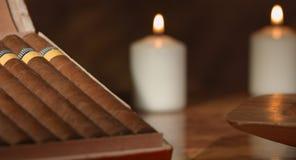 4K: Movimiento del resbalador de un cigarro cubano en un cenicero con algunas velas en el fondo a una caja abierta de cigarros en metrajes