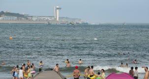 4k mucha gente en la playa arenosa apretada, gente que nada en el mar almacen de video