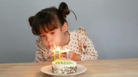 4K muchacha linda con la cara sonriente con la torta Vela del soplo para el partido de la celebración del cumpleaños en casa con  metrajes