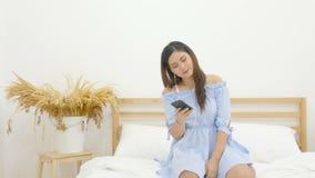 4K mujer asiática hermosa que se sienta en la cama que escucha la música con el auricular del uso en el teléfono móvil y el baile