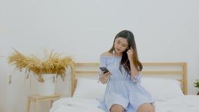 4K mujer asi?tica hermosa que se sienta en la cama que escucha la m?sica con el auricular del uso en el tel?fono m?vil y el baile