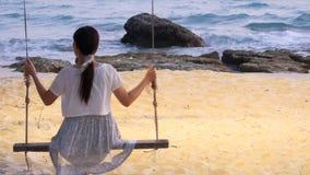 4K mujer que juega el oscilación debajo del árbol en la playa en el tiempo libre durante la oscuridad después de puesta del sol c metrajes