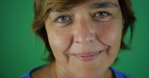 4k - Mulher de meia idade com piscadelas curtos e sorrisos de um corte de cabelo no verde video estoque