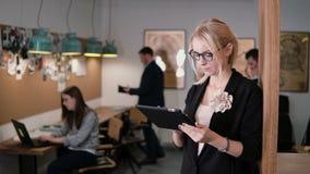 4K a mulher de negócios loura bonita nova do close up usa uma tabuleta do écran sensível no escritório startup moderno filme