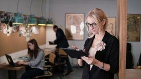 4K a mulher de negócios loura bonita nova do close up usa uma tabuleta do écran sensível no escritório startup moderno Fotografia de Stock