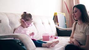 4k: Mutter und süßes Tochterspiel in den Doktoren Tochter setzt an Spielzeuggläser und schreibt Diagnose stock video