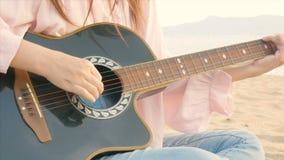 4K nah oben von der langen Haarfrau entspannen sich das Spielen der Akustikgitarre am Strand mit leichtem Wind während der Sonnen stock video footage
