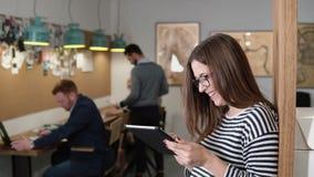 4K Nahaufnahme benutzt junge attraktive Brunettegeschäftsfrau eine Tablette des Bildschirm- im modernen Startbüro Lizenzfreies Stockfoto