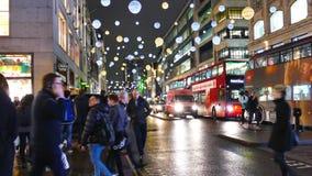 4k natt Timelapse av julljus och London bussar på stationen med folk som går på den upptagna Oxford gatan London arkivfilmer