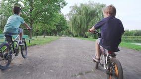 4K Niños, amigos que montan las bicis, bicicletas almacen de metraje de vídeo