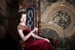 K?nigin im roten Kleid, das auf Thron sitzt Symbol der Energie und des Reichtums stockfotos