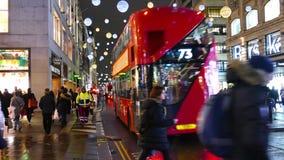 4k noite Timelapse de luzes de Natal e de ônibus de Londres na estação com os povos que andam na rua ocupada Londres de Oxford filme