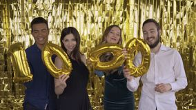 1k. The number 1000 of foil. 4 happy cheerful people at a party with balloons in their hands. A group of laughing people stock video footage