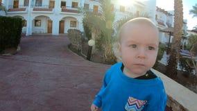 4k - o bebê pequeno bonito olha na câmera e nas caminhadas no movimento lento vídeos de arquivo