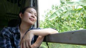 4K o curso asiático da mulher pelo trem que olha fora de uma janela do trem no começo railway do trem em Banguecoque vai a Kancha filme