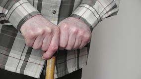 4k old elderly man with walking stick hard to stand up from the sofa, pernsion healthcare. Concept stock image