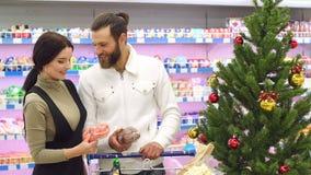 K?pande livsmedel f?r ung lycklig familj p? supermarket f?r jul arkivfilmer