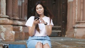 4k panning footage of beautiful smiling girl typing message on mobile phone while sitting on stone staircase. 4k panning video of beautiful smiling girl typing stock footage