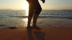4K panning mężczyzna bieg w płytkim morzu przy zmierzchem zbiory