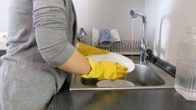 4k panning video van jonge vrouw in gele altexhandschoenen die schotels op keuken wassen stock videobeelden