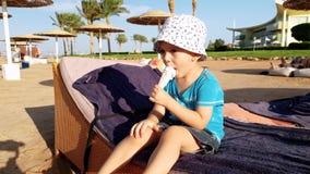 4k panning video van weinig peuterjongen die roomijs op lanterfanter op zee strand eten stock video