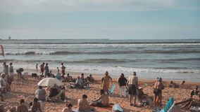 4 k panorama of the summer beach full of people at sunny warm day resting, taking sunbath made in blue orange color. Asturias, Gijon spain Cantabrian stock footage