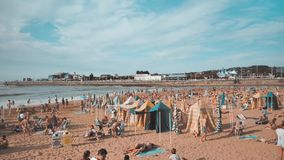 4 k panorama of the summer beach full of people at sunny warm day resting, taking sunbath made in blue orange color. Asturias, Gijon spain Cantabrian stock video footage