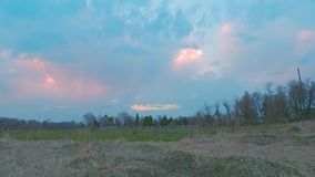 4k panoramic sunset time-lapse in a field in cloudy weather, visible church stock video