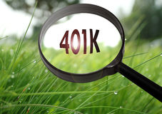 401k pension plan. Magnifying glass with the word 401k pension plan on grass background. Selective focus Stock Image