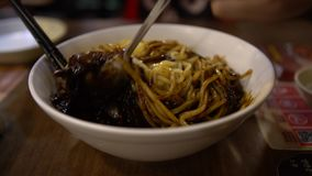 4K Jajangmyeon the Korean noodles in black bean sauce at a restaurant. 4K People eating the Jajangmyeon with chopsticks in a restaurant. Korean noodles in black stock footage
