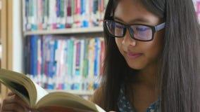 4K: Pequeños estudiantes asiáticos que leen un libro en biblioteca metrajes