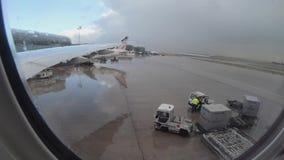 4K, personnel d'aéroport chargeant des conteneurs d'ULD à l'intérieur de l'avion à pleuvoir le jour banque de vidéos