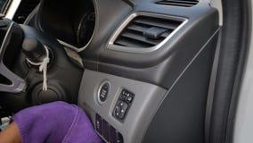4K perto disparou acima na mão da mulher que usa a micro tela roxa da fibra para limpar o interior do painel frontal do carro do  vídeos de arquivo