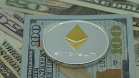 4K Physical metal silver Ethereum currency over 100 american dollar bill. 4K Physical metal silver Ethereum currency over 100 dollar bill of United States stock video footage